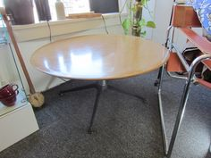 "This week our ""Pick"" is another great Mid-Century Modern Find. A great coffee table with a cast iron and chrome base. This vintage table is from the 1960's and measures 36″ in diameter and stands 17″ tall. The top of the table is made from Weyerhaeuser Forplex with a simulated wood grain finish."
