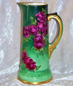 """Spectacular T & V Limoges, France Hand Painted 1900's floral tankard. It has been decirated with Vibrant & Lifelike """"Deep Red Roses"""" on stem and leaf against a background of shadow leafing and several shadesvof green. both font and back have been decorated all the way down to blooming rose buds. Heavy gold gilding has been added to the handle, base, top rim and inner rim."""