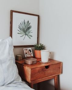 Example of a tightly fitting bedside table. But I see now I want to so with like flat IKEA Malm style 2 or 2 drawer so it's sleek and holds the most while looking th coolest, most chic. Love the idea of a large framed piece right above it and th greenery.  For Me Space I'd obv use rose gold tones and pink and silver to achieve these colors, just with a white side table