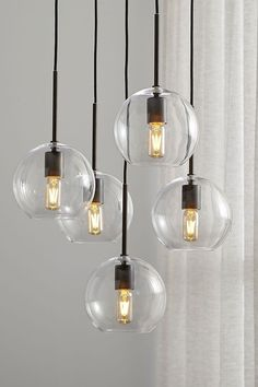 Clear spheres dangle a contemporary chandelier over dining room tables or kitchen islands. Dark bronze hardware adds contrast, while adjustable cord lengths create the right amount of stagger. Farmhouse Lighting, Dining Room Lighting, Kitchen Lighting, Home Lighting, Pendant Lighting, Lighting Ideas, Dining Room Design, Interior Design Kitchen, Dining Room Table
