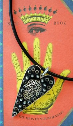 DIY craft project! Hamsa Hand in Heart Mosaic Necklace: All parts by www.rings-things.com.  Silver hamsa hand nestled inside a primitive art heart shape bezel along with sterling silver coated glass spikes, and aluminum heishi trade beads...  Black EnCapture Artisan Concrete holds it all together, and it is strung on a thick black licorice leather choker.