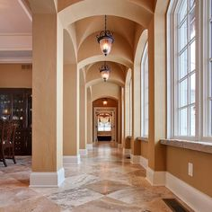 The #gallery of this #customhome  features #groin #vaults. We love how the lights align perfectly with the diagonal pattern #travertine tile. #Stone sills complete the old world look. #thefinesthomesanywhere #MartinBrothers #MarvinWindows