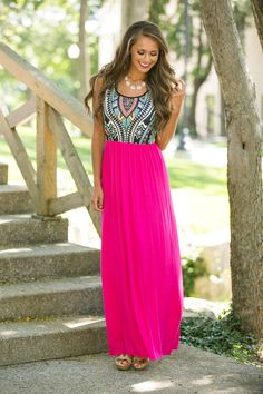 This wonderfully soft and vibrant maxi will make you the star of any event! The bright hot pink skirt pairs perfectly with the black, white, mint, yellow, red, and aqua print on the bodice for a stellar combination.