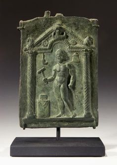 ROMAN BRONZE VOTIVE PLAQUE OF VULCAN, GOD OF THE FORGE. Standing nude within an aedicula, or shrine, with arched pediment supported by columns. In his right hand he holds a hammer about to strike and anvil atop an altar; in his left a pair of tongs. 2nd-3rd Century CE