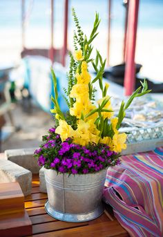 Buffet arrangement with yellow gladiolus and fuchsia mums in a wide tin pot
