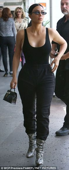 Strutting her stuff: Kim accessorized with a mini bag and narrow sunglasses...