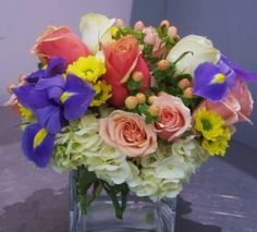 A beautiful pastel arrangement with Spray Roses, Iris', Yellow Rovers, Roses, Hydrangea and Hypericum Berry from Flowers of Charlotte