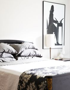 Serene, grayscale bedroom with black-and-white photograph and stacked gray pillows