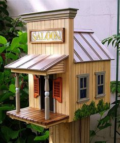 The SALOON Birdhouse has hand carved plank walls and front porch. Turned post and carved swinging doors. Theres a hand painted, framed sign and a stovepipe chimney. It is 11 High x 10 3/4 Deep x 7 1/4 Wide. Price- $165.