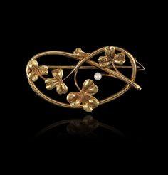 Broche en or jaune (18k) formant un lien enroulé se terminant par des feuilles de trèfles rehaussées d'une perle de culture. Art Nouveau or Art Nouveau Style.