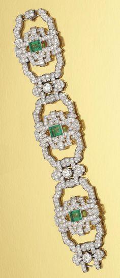 EMERALD AND DIAMOND BRACELET, 1930S.  Designed as a series of open work geometric links millegrain-set with circular-cut and baguette diamonds, each alternately set to the centre with a collet-set step-cut emerald and circular-cut diamond respectively, length approximately 190mm.