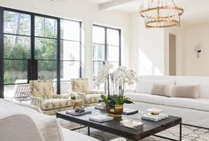 White and gray living room features a tiered brass candelabra chandelier illuminating white wingback sofas lined with gray lumbar pillows facing each other across from a distressed black coffee table atop a gray trellis rug.