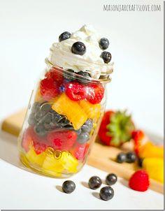 Fruit Salad in a Mason Jar mason jar.  pineapples on the bottom strawberries blueberries melon raspberries dollop of whipped cream