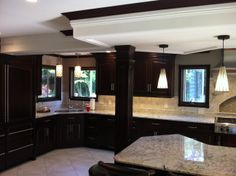 Double raised-panel columns are used to hide conduit in this kitchen. The soft maple is stained to match the new island and existing cabinetry. Column Wrap, Wooden Columns, Raised Panel, Fireplace Surrounds, Cladding, Basement, Island, Architecture, Interior