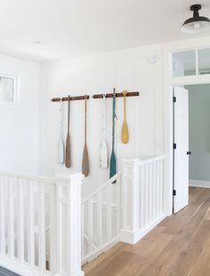 Oar rack wall decor. Cottage entry wall decor. Board and batten walls, white oak flooring and chippy vintage oars on oar racks.