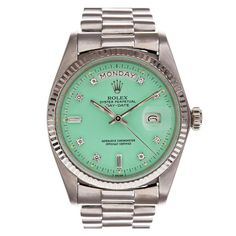 a rolex with a seafoam green face. dying.