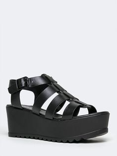 - These cage sandals will elevate your look and your mood! - Platform sandals have a vegan leather upper with a t-strap design and a buckle closure on the side. - Non-skid sole and cushioned footbed.