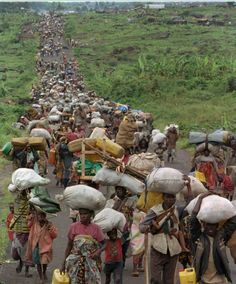 FILE - In this Friday, Nov. 15, 1996 file photo, hundreds of refugees stream out of the Mugunga refugee camp in Zaire heading toward the Rwanda border as Zairian rebels moved in to occupy the camp. About 100,000 Rwandan refugees and displaced Zairians began streaming back home Friday, apparently freed from the control of Hutu militias. (AP Photo/David Guttenfelder)