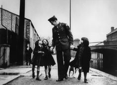 """An American soldier with war """"adopted"""" orphans, London, 1943."""