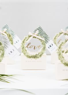 """Love"""" in metallic gold is framed with a delicate wreath of greenery. The meticulous details in this exclusive little favor box will add instant. Green Weddings, Favor Boxes, Favours, Metallic Gold, Greenery, Sweet Treats, Delicate, Ribbon, Miniatures"""