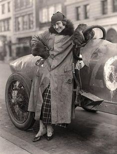 The photograph illustrates Miss Elinor Blevins beside her race car. 1915