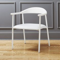 Shop thea white faux leather chair.   Designed by Euga Design Studio, Thea is minimalism with a twist.  Sleek and sculptural, hand-carved ashwood back sits atop a metal tube frame and engineered legs—-all powdercoated bright white.