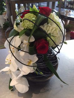 Arrangement with orchids and red roses - by Moens Flowers