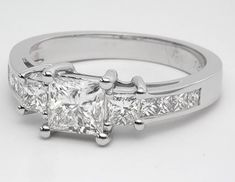 Exceptionally crafted, this engagement ring is a dazzling combination of styles that blend perfectly together. 8 channel-set princess cut diamonds decorate the side of the band and come up to meet the 2 bigger princess cut side stones at the top. In between the 2 side stones will be your center stone, a princess cut diamond of your choice.