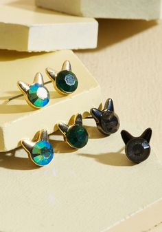 Take Meow-t Tonight Earring Set | Mod Retro Vintage Earrings | ModCloth.com These little stud earrings are so sassy, they're just begging to be worn! And, you simply can't turn them down. Touting green, iridescent, and silver faux gems all topped with either gold or pewter-hued cat ears, these studs are always ready to befriend your favorite fancy looks!