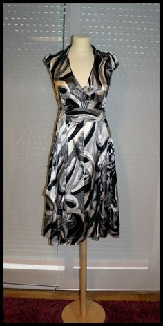 Vestido en tonos negros, grises y blancos. Con escote en V, atado a la cintura y falda evasé. Sienta genial.  Marca Zara, T-S PVP 24,99 eur.