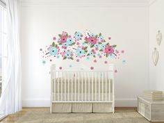 An assortment of bubblegum coloured flower decals on a white wall behind a white crib.