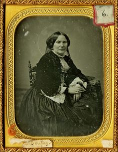 Woman wearing fancy lace edged belled undersleeves and a fringed jacket. Enlarged reproduction of a 1/4 plate daguerreotype, circa 1856.