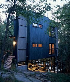Scrap steel and reclaimed wood clad the three-story triangular tower, which hovers over a small deck and outdoor space. Photo by Paul Orenstein