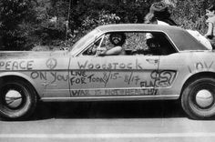 A music fan at Woodstock shows off his car, which is covered in anti-war slogans for love and peace, 1969.