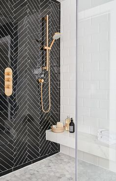 Black herringbone marble tile feature wall in shower || Feature walls that make a stunning design statement - FIRST SENSE