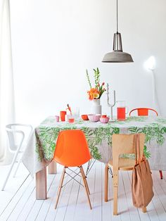 orange and green accents in white dining area