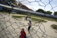 "Children practice during a baseball game at the ""Mamera"" neighborhood in Caracas March 10, 2011.  REUTERS/Jorge Silva"