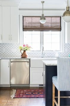 Gorgeous white and blue kitchen is fitted with a red and blue kilim runner placed on dark stained oak floors in front of a white cabinets topped with marble countertops holding a farmhouse sink with a polished nickel gooseneck faucet in front of a window dressed in a bamboo roman shade and accented with Home Depot Merola Tiles Arabesque Glossy White backsplash tiles lit by a Small Hick Pendant.