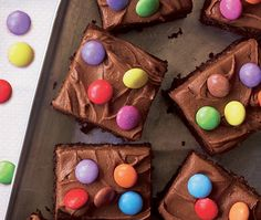 Squares of chocolate cake topped in multi-coloured smarties