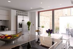 Kitchen looking out to the garden patio: A modern family home in London, by NS Interiors