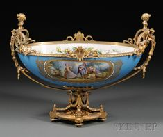 Sevres Ormolu-mounted Porcelain Center Bowl, France, 19th century, the bowl interior with flowers and central motif of hand-painted straw hat, bouquet, and insects, bowl exterior with blue ground centering a scene of child courtiers, with a further bouquet on the reverse, flanked by scrolling handles set with babe-bust finials, on reticulated oval base with four outset fee