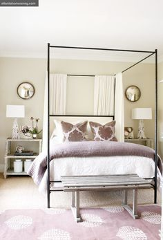 Bedroom with iron four poster bed and upholstered headboard. Neutral colors with purple accents. In love with this bed.