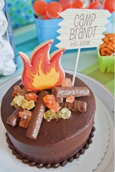 This DIY campfire cake is the perfect addition to a summer camp-themed birthday party. Use chocolate candy bars as logs and rock candy for embers, and you've got your very own edible campfire! Your adventurous toddler will love creative ideas like a cardboard canoe race or a tie-dye t-shirt station. For more great party ideas, check out the rest of this post. #themedcakes