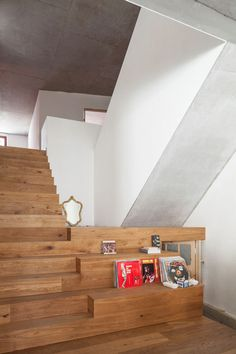 This apartment features a wooden staircase with widened treads that provide storage and casual seating areas