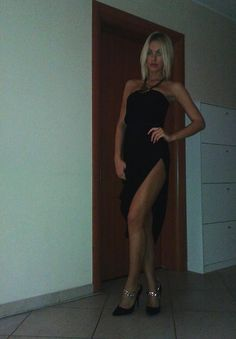 Tall, pretty and slim blonde woman in black long gown & heels