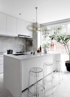 White kitchen + ghost chairs