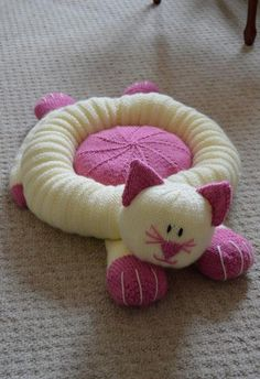 Knitting pattern instructions to the Cat SnugglerThis unusual design will work as a cat bed or cushion for a child.Yarn : Chunky / bulky. 400g cream, 200g pink. Oddment of black. Stuffing.Needle Size : 4.5mm Single Point NeedlesMain Colours : Pink and CreamDimensions : Approximately 60cm from toe to toe. Inner cushion 25cm diameter. Outer ring approx. 44cm diameter.Skills used : Cast on, knit, purl, increase by knitting into the front and back of stitch, decrease by knitting two stitche...