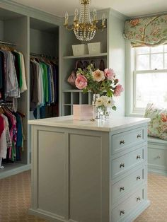 Shabby chic closet features green built-ins fitted with shelves and cubbies next to a gray built-in window seat bench adorned with pink and green floral pillows.