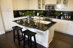 Black and white themes never go out of style and can always look fresh and crisp. Shiny black countertops and a bright white cabinet finish ...
