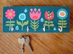 DIY key rack made with printed paper. So cute, inexpensive and customizable! I wonder if something similar, with stronger hooks, would work for coats/backpacks? Car Key Holder, Key Chain Holder, Key Holders, Key Rack, Key Organizer, Idee Diy, Paper Decorations, Diy Tutorial, Diy And Crafts
